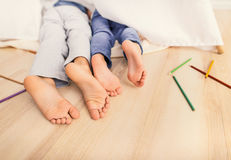 Gambe del bambino sotto la coperta bianca Immagini Stock