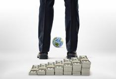 Gambe del primo piano con i pacchetti dei dollari e di piccolo globo Fotografia Stock Libera da Diritti