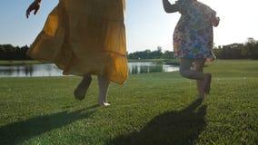 Gambe del primo piano di funzionamento del bambino e della madre sull'erba stock footage