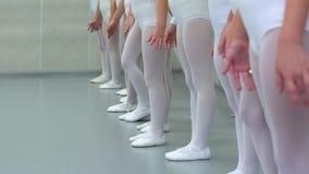 Gambe del primo piano di piccolo gruppo delle ballerine in scarpe bianche nella fila che pratica a scuola di balletto classico video d archivio