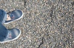 Gambe del ` s dei bambini su un fondo della ghiaia Fotografia Stock Libera da Diritti