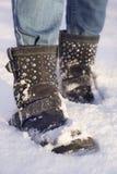 Gambe del ` s della donna con le blue jeans e le scarpe nere in una neve Fotografie Stock Libere da Diritti