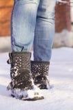 Gambe del ` s della donna con le blue jeans e le scarpe nere in una neve Fotografie Stock