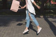 Gambe del ` s della donna Donna di salto con la borsa Fotografie Stock Libere da Diritti