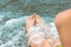 Gambe del ` s della ragazza nell'acqua di mare di estate immagini stock