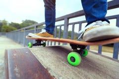 Gambe del skateboarder che guidano pattino allo skatepark della città Immagine Stock