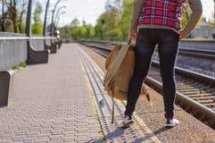 Gambe del treno in attesa della ragazza con backback Fotografia Stock Libera da Diritti