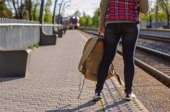 Gambe del treno in attesa della ragazza con backback Fotografia Stock