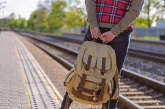 Gambe del treno in attesa della ragazza con backback Fotografie Stock Libere da Diritti