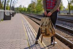 Gambe del treno in attesa della ragazza con backback Fotografie Stock