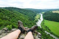 Gambe del viaggiatore che si siedono su una cima dell'alta montagna e che considerano il paesaggio del fiume Concetto naturale di Fotografie Stock Libere da Diritti