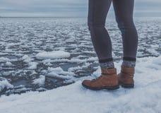 Gambe del viaggiatore sulla neve con la vista congelata del mare fotografia stock