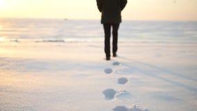 Gambe dell'uomo che camminano sulla neve con le orme il giorno nevoso archivi video