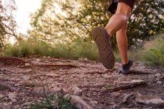 Gambe dell'uomo che corrono sulla traccia nelle montagne fotografia stock