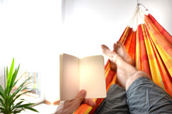 Gambe dell'uomo che si riposano in amaca dell'interno che tiene il libro di avviso vuoto in sua mano Fotografia Stock Libera da Diritti