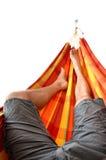 Gambe dell'uomo che si riposano in amaca luminosa isolata su fondo bianco Fotografia Stock