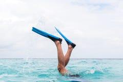 Gambe dell'uomo con le alette che si tuffano nell'acqua immagini stock libere da diritti