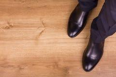 Gambe dell'uomo d'affari sul parquet, vista superiore Immagini Stock Libere da Diritti