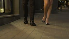 Gambe dell'uomo e della donna che camminano verso la macchina fotografica, coppia che va bastonare, notte fuori archivi video