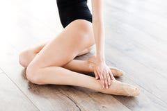 Gambe della ballerina della donna che si siedono sul pavimento a scuola di balletto Fotografia Stock