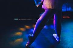 Gambe della ballerina nei pointes sul pavimento di parquet su fondo scuro immagine stock