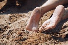 Gambe della donna che pongono alla spiaggia Fotografie Stock