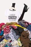 Gambe della donna che raggiungono fuori da un grande mucchio dei vestiti con una maglietta che non dice niente durare Fotografia Stock