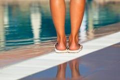 Gambe della donna che stanno sull'orlo della piscina Immagini Stock