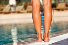 Gambe della donna che stanno sull'orlo della piscina Fotografie Stock