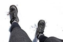 Gambe della donna con i piedi sulla neve fotografia stock libera da diritti