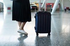 Gambe della donna del viaggiatore che camminano portando una valigia in un aeroporto fotografie stock libere da diritti