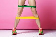 Gambe della donna dell'istruttore di forma fisica che esercitano risolvere con la banda di gomma verde e gialla di resistenza sul immagine stock libera da diritti