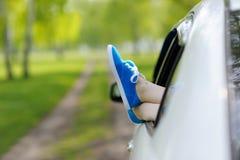 Gambe della donna fuori Windows nell'automobile fra gli alberi Immagini Stock