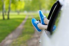 Gambe della donna fuori Windows nell'automobile fra gli alberi Immagine Stock Libera da Diritti