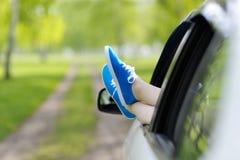 Gambe della donna fuori Windows nell'automobile fra gli alberi Fotografia Stock Libera da Diritti