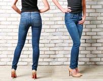 Gambe della donna in jeans sul fondo del muro di mattoni Fotografia Stock