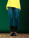 Gambe della donna negli stivali dei pantaloni del denim Fotografia Stock