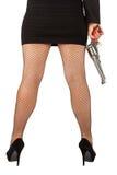 Gambe della donna pericolosa con la rivoltella e le scarpe nere Fotografie Stock