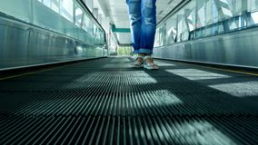 Gambe della donna in sandali che stanno sul passaggio pedonale automatico, sulla scala mobile alla stazione della metropolitana d stock footage
