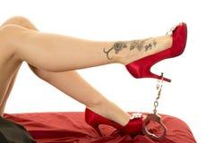 Gambe della donna in scarpe rosse con un tatuaggio e le manette Immagini Stock Libere da Diritti