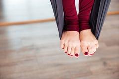Gambe della donna sull'amaca che fa yoga aerea Immagine Stock