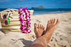 Gambe della donna sulla spiaggia di tramonto Immagini Stock