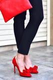 Gambe della donna, tacchi alti rossi e borsa Colpo esterno di modo Fotografia Stock