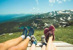 Gambe della famiglia del viaggiatore che riposano su un'alta montagna Immagini Stock Libere da Diritti