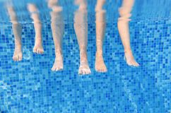 Gambe della famiglia subacquee nella piscina, nuotata con i bambini nell'ambito del concetto divertente dell'acqua, vacanza con i fotografie stock libere da diritti