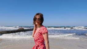 Gambe della giovane donna che camminano sulla spiaggia sabbiosa con le forti onde Giovane donna che porta vestito rosso che cammi archivi video