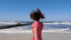 Gambe della giovane donna che camminano sulla spiaggia sabbiosa con le forti onde Giovane donna che porta vestito rosso che cammi stock footage