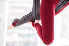 Gambe della giovane donna facendo uso dell'amaca e del fare gli esercizi aerei di yoga Immagine Stock