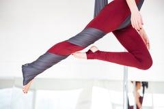 Gambe della giovane donna in leggins che praticano yoga aerea allo studio Immagini Stock