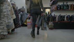 Gambe della giovane donna in talloni che camminano in un centro commerciale del negozio di vestiti mentre le mani sono piene dei  stock footage